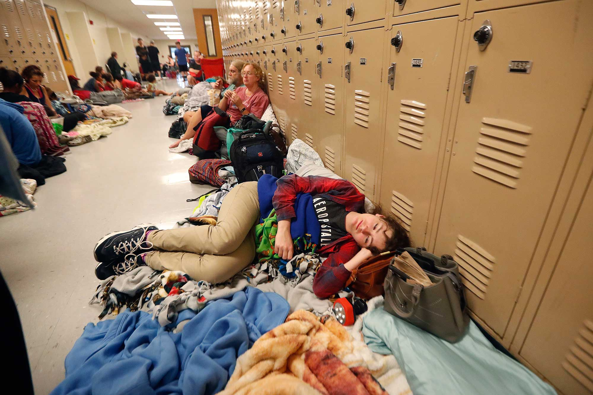 <div class='meta'><div class='origin-logo' data-origin='none'></div><span class='caption-text' data-credit='Gerald Herbert/AP Photo'>Emily Hindle lies on the floor at an evacuation shelter set up at Rutherford High School, in advance of Hurricane Michael on Wednesday.</span></div>