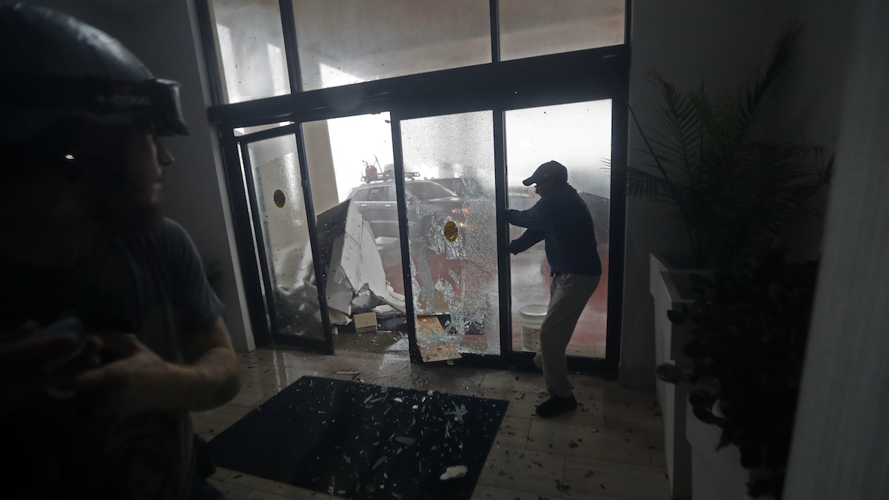 <div class='meta'><div class='origin-logo' data-origin='AP'></div><span class='caption-text' data-credit='AP Photo/Gerald Herbert'>A hotel employee holds a glass door closed as it breaks from flying debris during Hurricane Michael in Panama City Beach, Fla., Wednesday, Oct. 10, 2018.</span></div>