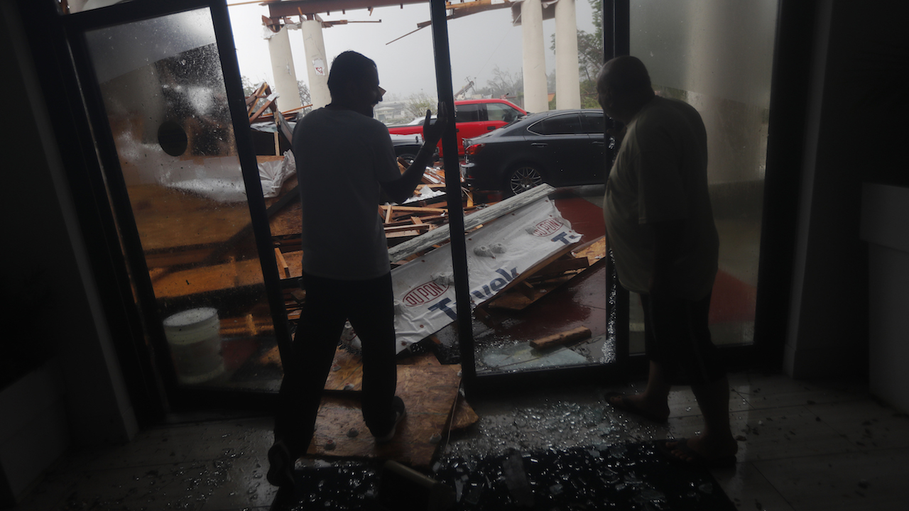 <div class='meta'><div class='origin-logo' data-origin='AP'></div><span class='caption-text' data-credit='AP Photo/Gerald Herbert'>Hotel employees look at a canopy that just collapsed, as Hurricane Michael passes through in Panama City Beach, Fla., Wednesday, Oct. 10, 2018.</span></div>