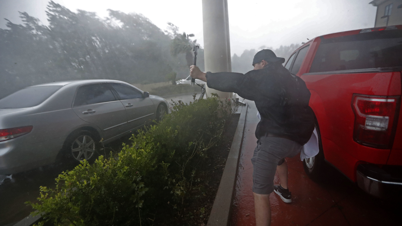 <div class='meta'><div class='origin-logo' data-origin='AP'></div><span class='caption-text' data-credit='AP Photo/Gerald Herbert'>A storm chaser films from underneath a hotel canopy during Hurricane Michael in Panama City Beach, Fla., Wednesday, Oct. 10, 2018.</span></div>