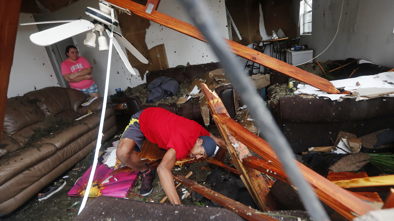 <div class='meta'><div class='origin-logo' data-origin='AP'></div><span class='caption-text' data-credit='AP Photo/Gerald Herbert'>Dorian Carter looks under furniture for a missing cat after several trees fell on their home during Hurricane Michael in Panama City, Fla., Wednesday, Oct. 10, 2018.</span></div>