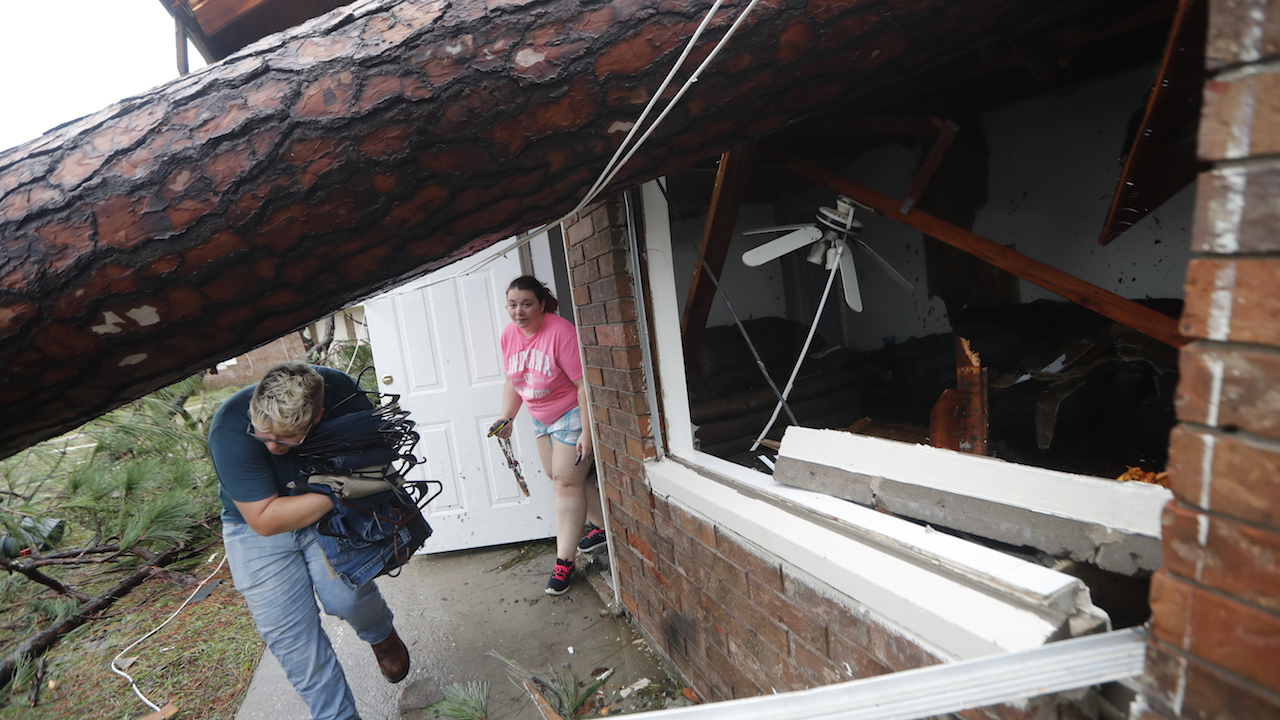 <div class='meta'><div class='origin-logo' data-origin='AP'></div><span class='caption-text' data-credit='AP Photo/Gerald Herbert'>Megan Williams, left, and roommate Kaylee O'Brian take belongings from their destroyed home after several trees fell on the house during Hurricane Michael.</span></div>