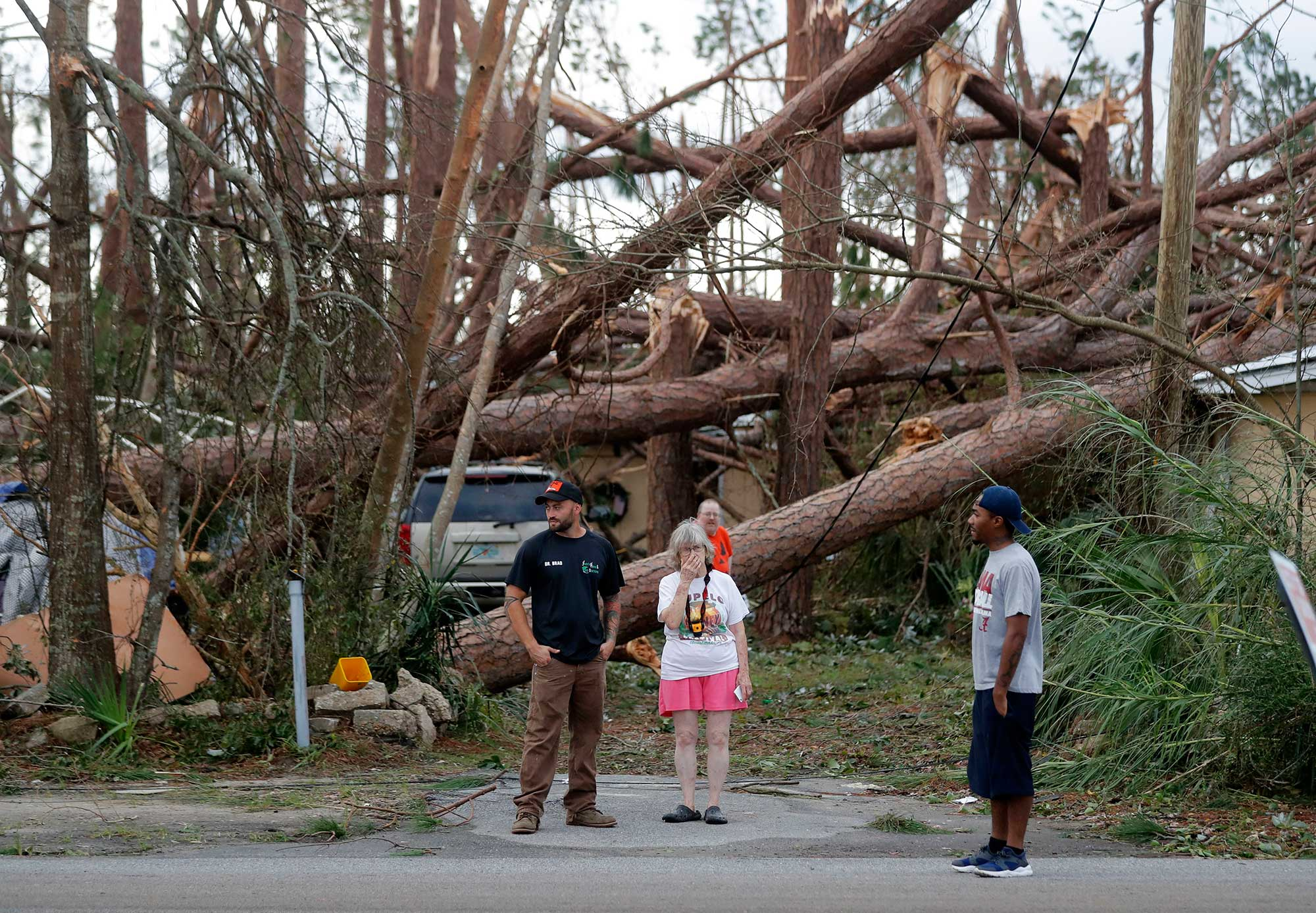 <div class='meta'><div class='origin-logo' data-origin='none'></div><span class='caption-text' data-credit='Gerald Herbert/AP Photo'>Joyce Fox, center stands in front of her heavily damaged home in the aftermath of Hurricane Michael in Panama City, Fla., Thursday, Oct. 11, 2018.</span></div>