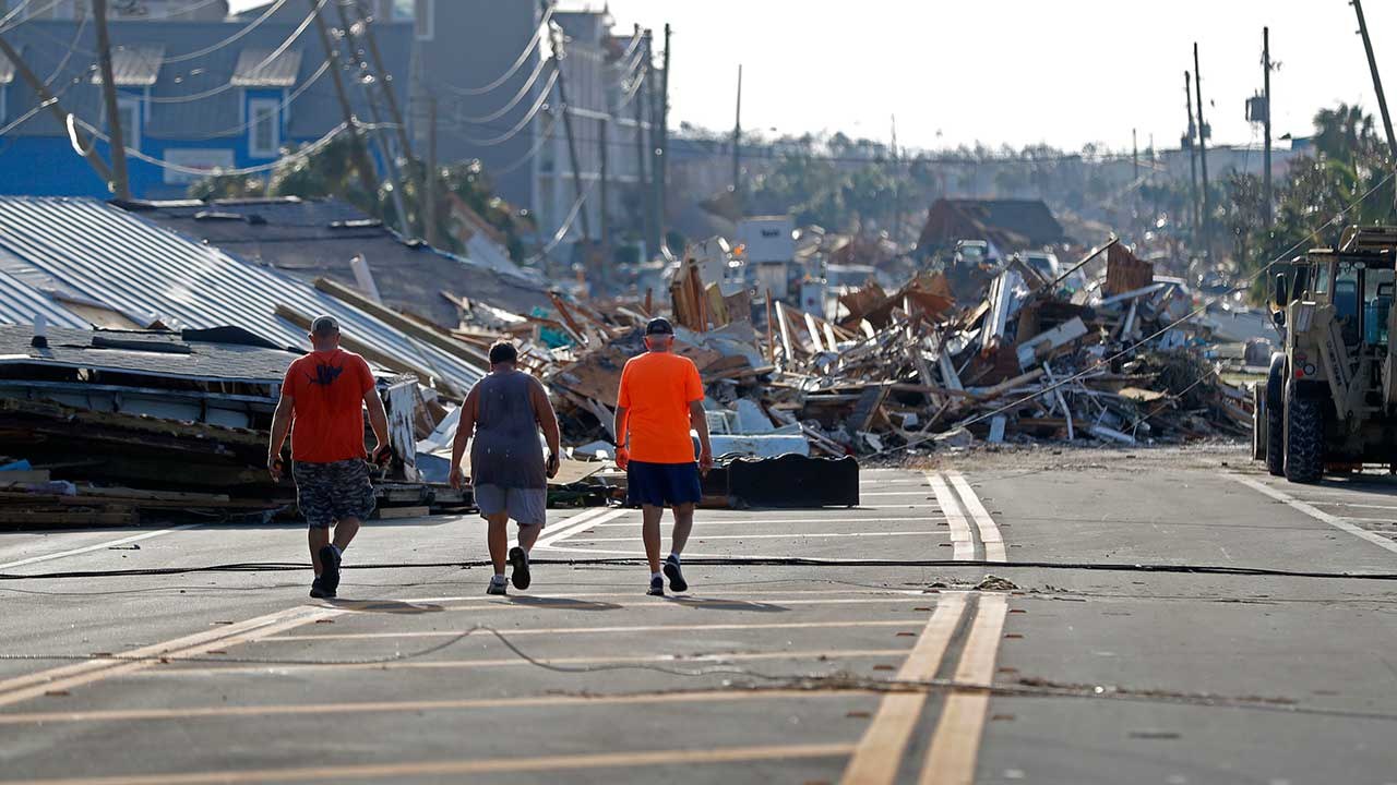 <div class='meta'><div class='origin-logo' data-origin='none'></div><span class='caption-text' data-credit='Gerald Herbert/AP Photo'>People walk amidst destruction on the main street of Mexico Beach, Fla., in the aftermath of Hurricane Michael on Thursday, Oct. 11, 2018.</span></div>