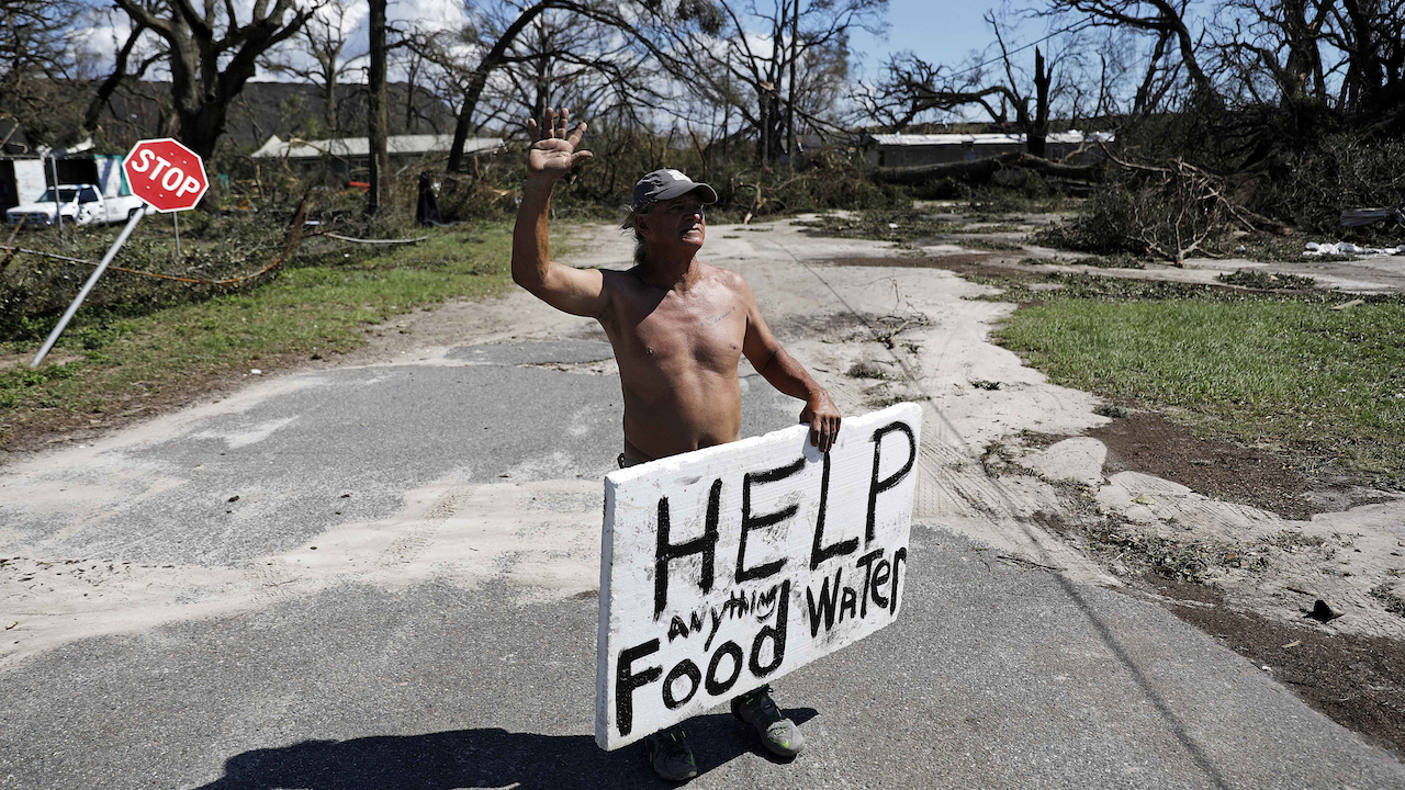 <div class='meta'><div class='origin-logo' data-origin='AP'></div><span class='caption-text' data-credit='AP Photo/David Goldman'>Michael Williams, 70, waves to passing motorists while looking for food and water in the aftermath of Hurricane Michael in Springfield, Fla.</span></div>