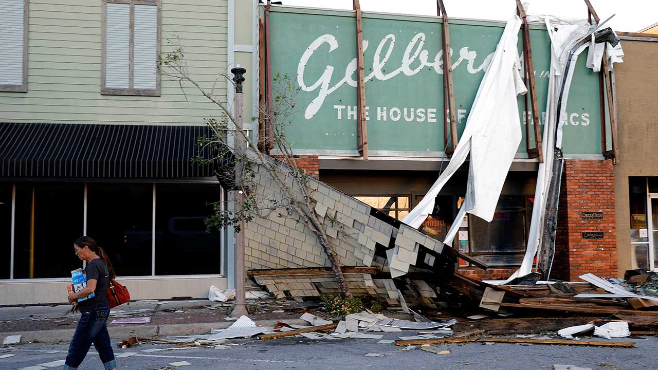 <div class='meta'><div class='origin-logo' data-origin='none'></div><span class='caption-text' data-credit='David Goldman/AP Photo'>A woman walks past a damaged building in the historical downtown district in the aftermath of Hurricane Michael in Panama City, Fla., Friday, Oct. 12, 2018.</span></div>
