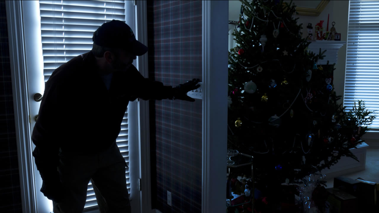 This photo illustrates a burglary or thief breaking into a home at night through a back door during the Christmas Holiday Season.