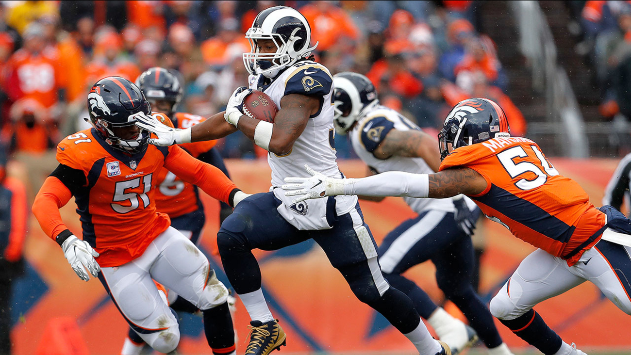 Rams running back Todd Gurley carries the ball as he's chased by two Bronco linebackers during a game in Denver on Sunday, Oct. 14, 2018.