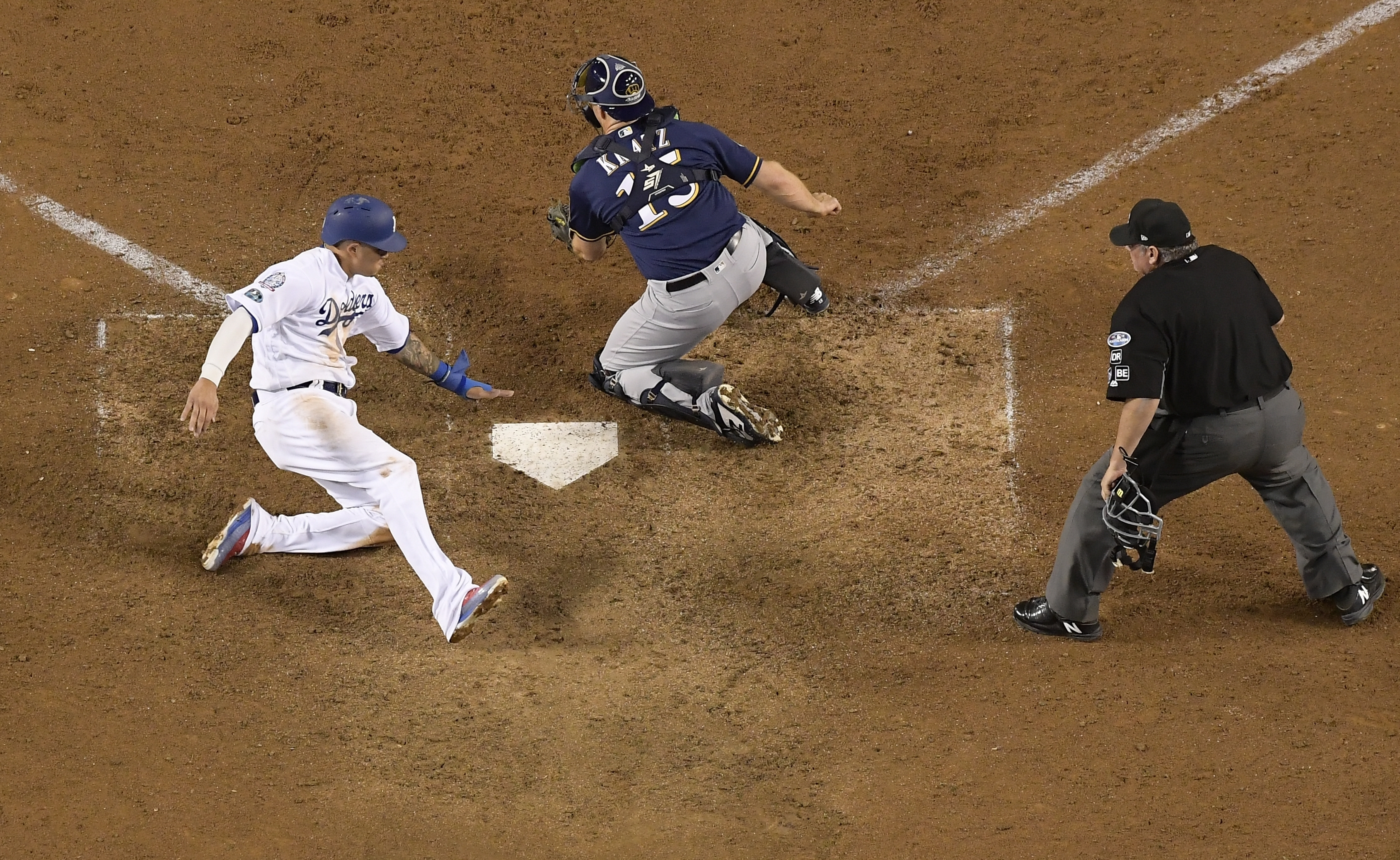 <div class='meta'><div class='origin-logo' data-origin='AP'></div><span class='caption-text' data-credit='AP Photo/Mark J. Terrill'>Dodgers' Manny Machado scores past Milwaukee Brewers catcher Erik Kratz during the 13th inning of Game 4 of the NLCS.</span></div>