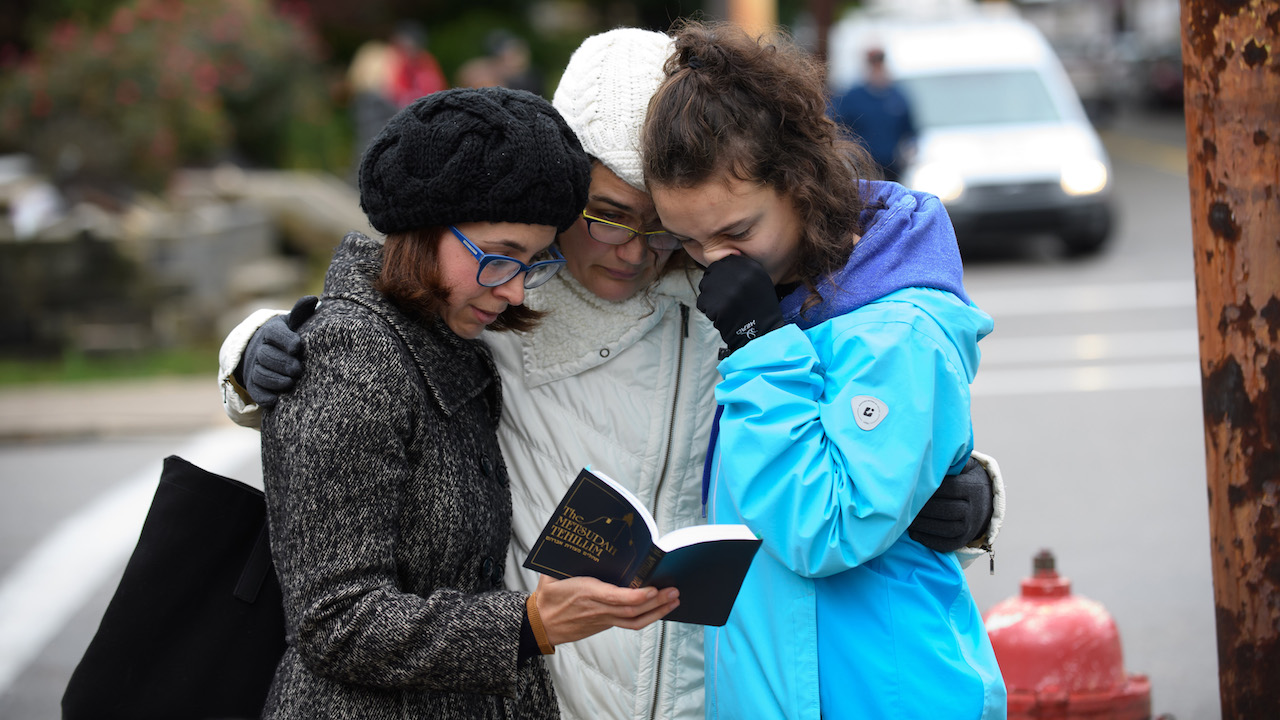 "<div class=""meta image-caption""><div class=""origin-logo origin-image ktrk""><span>ktrk</span></div><span class=""caption-text"">Tammy Hepps, Kate Rothstein and her daughter, Simone Rothstein, 16, pray from a prayerbook a block away from the site of a mass shooting at the Tree of Life Synagogue. (Jeff Swensen/Getty Images)</span></div>"