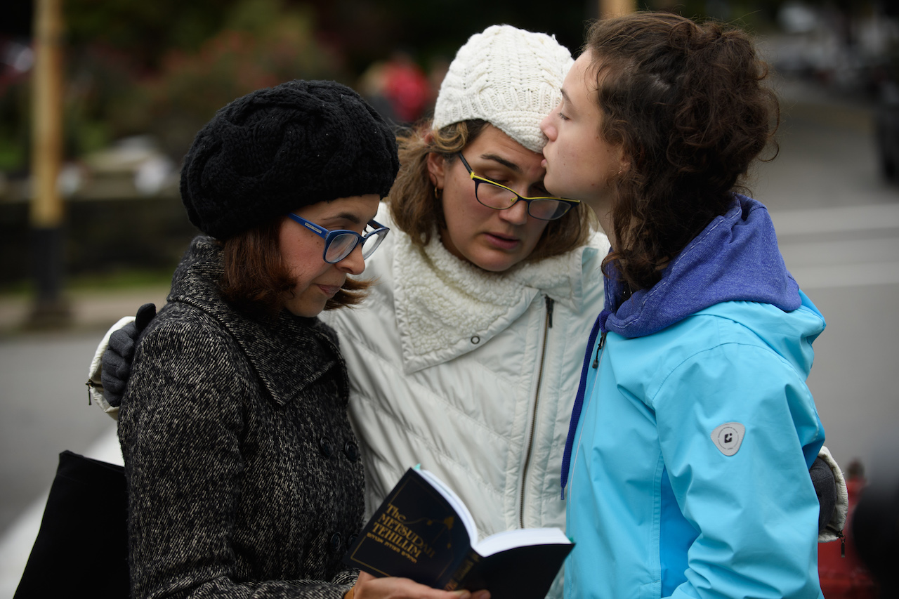 "<div class=""meta image-caption""><div class=""origin-logo origin-image wpvi""><span>wpvi</span></div><span class=""caption-text"">Tammy Hepps, Kate Rothstein and her daughter, Simone Rothstein, 16, pray from a prayerbook a block away from the site of a mass shooting at the Tree of Life Synagogue. (Jeff Swensen/Getty Images)</span></div>"