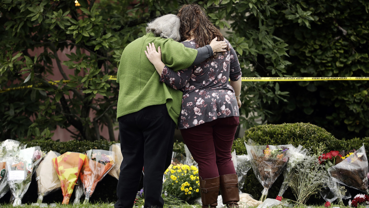 <div class='meta'><div class='origin-logo' data-origin='AP'></div><span class='caption-text' data-credit='AP Photo/Matt Rourke'>Two people support each other in front of flowers at a makeshift memorial at the Tree of Life Synagogue in Pittsburgh, Sunday, Oct. 28, 2018.</span></div>