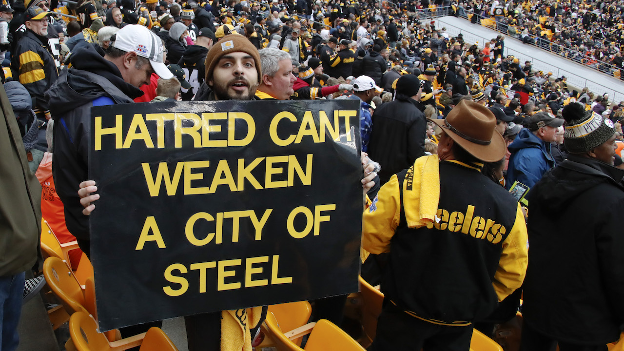 <div class='meta'><div class='origin-logo' data-origin='AP'></div><span class='caption-text' data-credit='AP Photo/Gene J. Puskar'>A Pittsburgh Steelers fan holds a sign honoring the victims of a deadly shooting spree at a synagogue on Saturday during the second half of an NFL football game.</span></div>