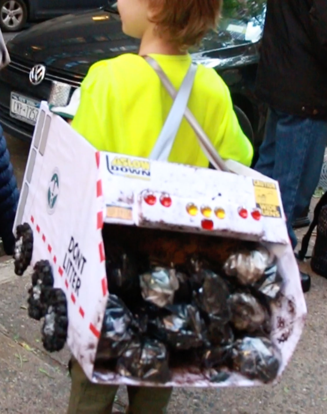 <div class='meta'><div class='origin-logo' data-origin='none'></div><span class='caption-text' data-credit=''>A boy who loves transportation dressed as a garbage trunk with bags in the back.</span></div>