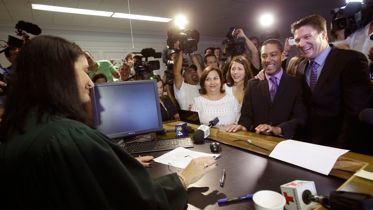 A lesbian and gay couple, center, smile after getting married by Miami-Dade Circuit Judge Sarah Zabel, left, Monday, Jan. 5, 2015 in Miami.