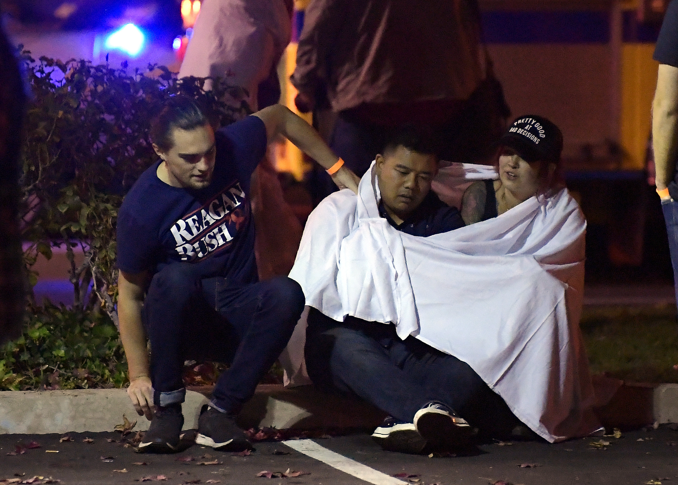 <div class='meta'><div class='origin-logo' data-origin='none'></div><span class='caption-text' data-credit='AP Photo/Mark J. Terrill'>People comfort each other after gunman opens fire on a nightclub in California, killing at least 11.</span></div>