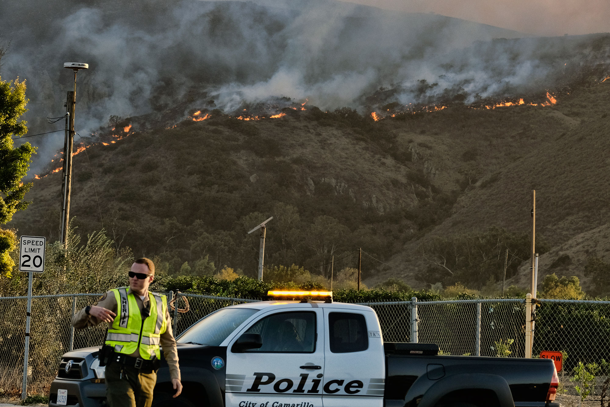 <div class='meta'><div class='origin-logo' data-origin='none'></div><span class='caption-text' data-credit='Richard Vogel/AP Photo'>A police officer directs traffic at a checkpoint in front of an advancing wildfire Thursday, Nov. 8, 2018, near Newbury Park, Calif.</span></div>