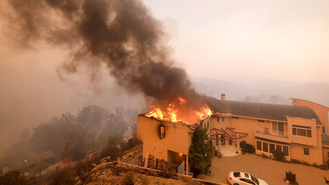 <div class='meta'><div class='origin-logo' data-origin='AP'></div><span class='caption-text' data-credit='AP Photo/Ringo H.W. Chiu'>A wildfire burns a home near Malibu Lake in Malibu, Calif., Friday, Nov. 9, 2018.</span></div>