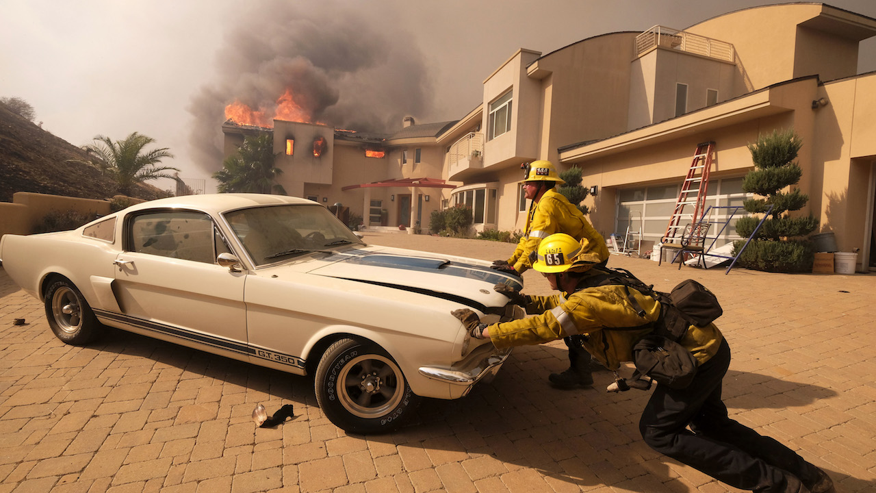 <div class='meta'><div class='origin-logo' data-origin='AP'></div><span class='caption-text' data-credit='AP Photo/Ringo H.W. Chiu'>Firefighters push a vehicle from a garage as the Woolsey fire burning a home near Malibu Lake in Malibu, Calif., Friday, Nov. 9, 2018.</span></div>