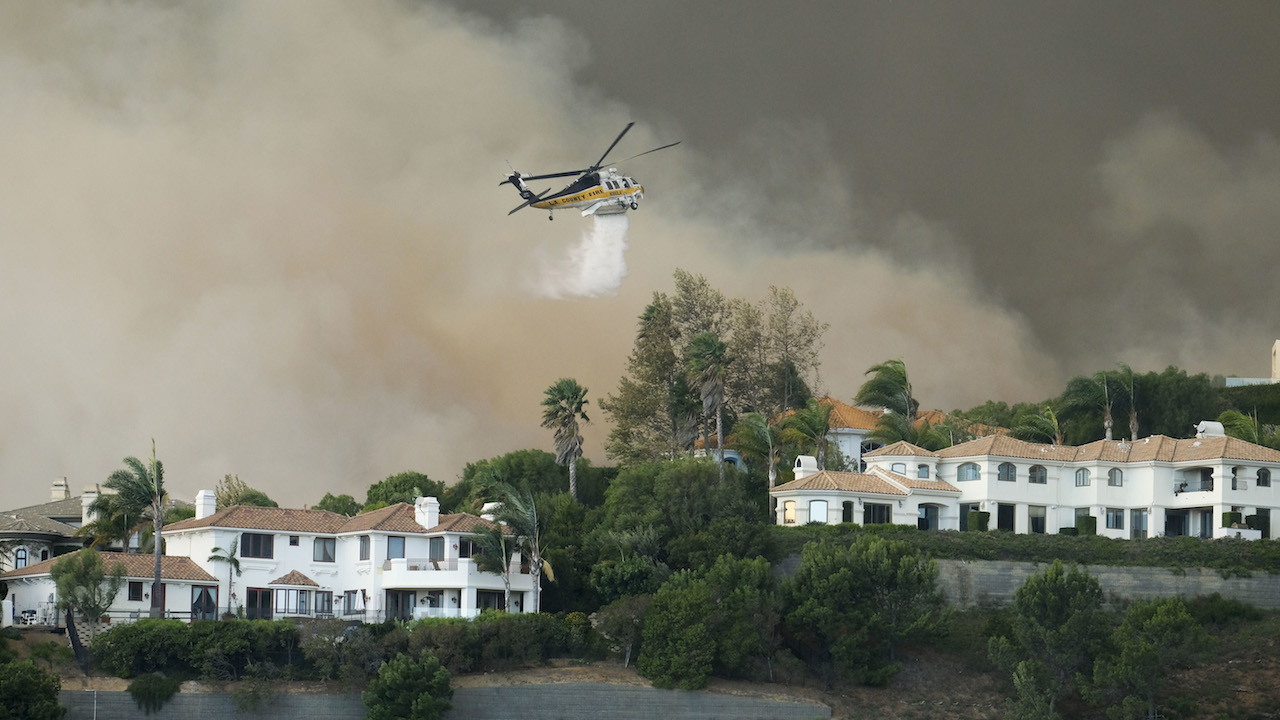 <div class='meta'><div class='origin-logo' data-origin='AP'></div><span class='caption-text' data-credit='AP Photo/Ringo H.W. Chiu'>A helicopter drops water on a brush fire behind homes during the Woolsey Fire in Malibu, Calif., Friday, Nov. 9, 2018.</span></div>