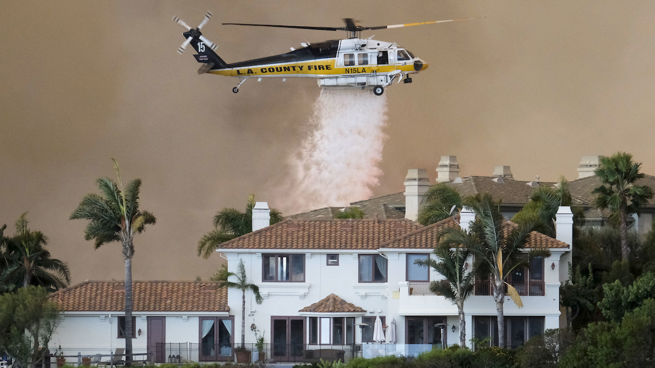 <div class='meta'><div class='origin-logo' data-origin='AP'></div><span class='caption-text' data-credit='AP Photo/Ringo H.W. Chiu'>A helicopter drops water on a brush fire behind a home during the Woolsey Fire in Malibu, Calif., Friday, Nov. 9, 2018.</span></div>