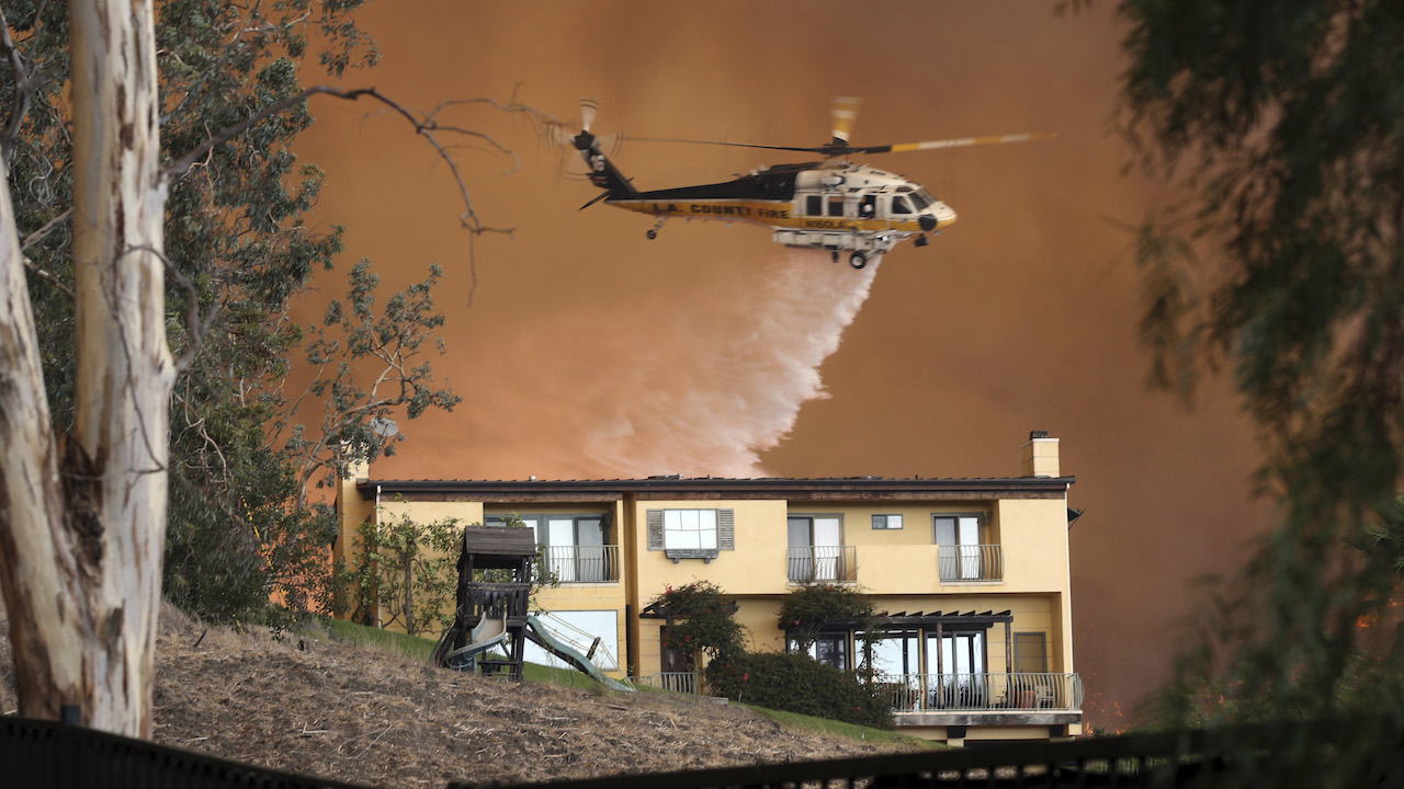 <div class='meta'><div class='origin-logo' data-origin='AP'></div><span class='caption-text' data-credit='AP Photo/Reed Saxon'>A Los Angeles County Fire Department helicopter makes a water drop on flames behind a home in Malibu, Calif., Friday, Nov. 9, 2018.</span></div>