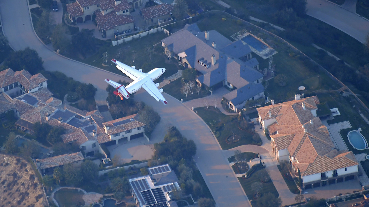 <div class='meta'><div class='origin-logo' data-origin='AP'></div><span class='caption-text' data-credit='AP Photo/Mark J. Terrill'>An air tanker gets ready to drop flame retardant to protect multimillion-dollar homes from fires Friday, Nov. 9, 2018, as seen from a helicopter.</span></div>