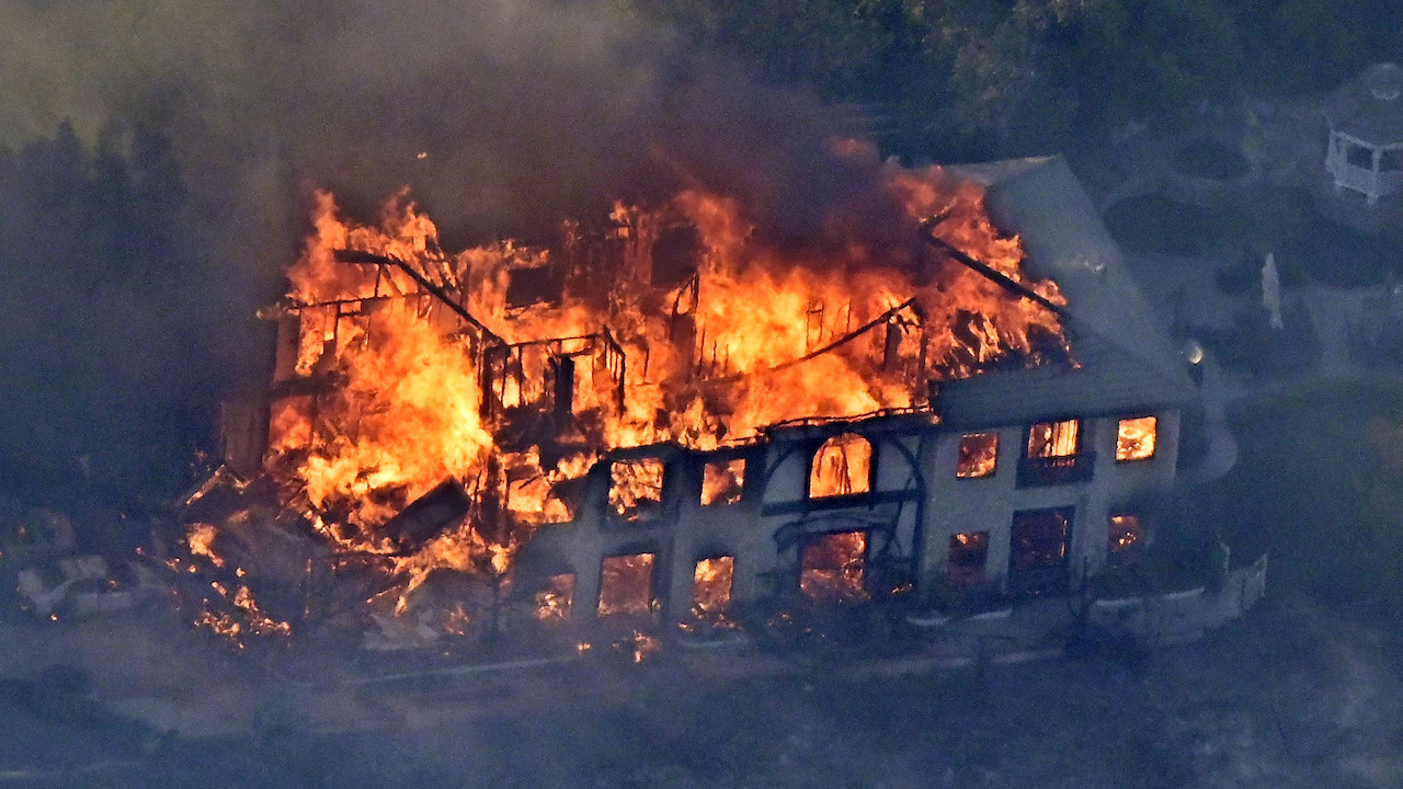 <div class='meta'><div class='origin-logo' data-origin='AP'></div><span class='caption-text' data-credit='AP Photo/Mark J. Terrill'>A home burns Friday, Nov. 9, 2018, as seen from a helicopter in the Calabasas section of Los Angeles.</span></div>