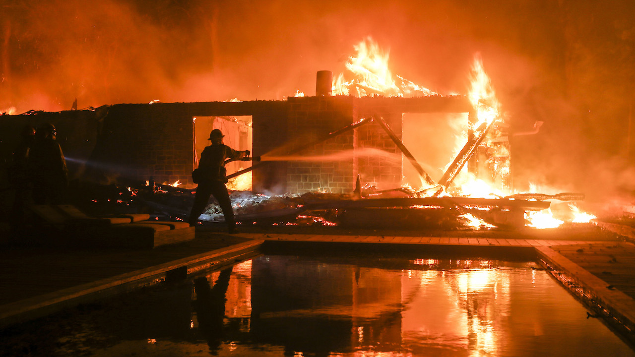 <div class='meta'><div class='origin-logo' data-origin='AP'></div><span class='caption-text' data-credit='AP Photo/Ringo H.W. Chiu'>A firefighter battles the Woolsey Fire burning a home in Malibu, Calif., Friday, Nov. 9, 2018.</span></div>