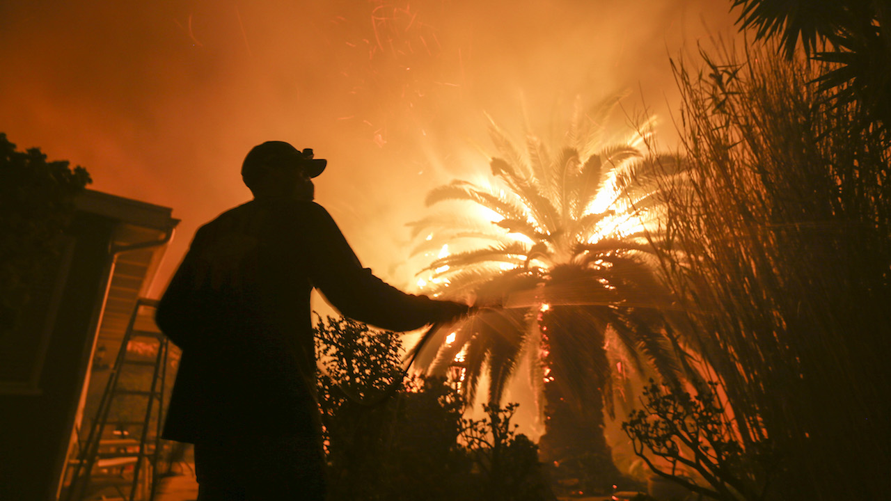 <div class='meta'><div class='origin-logo' data-origin='AP'></div><span class='caption-text' data-credit='AP Photo/Ringo H.W. Chiu'>Park Billow, 27, sprays water on the hot spots in his backyard as the Woolsey Fire burns in Malibu, Calif., Friday, Nov. 9, 2018.</span></div>