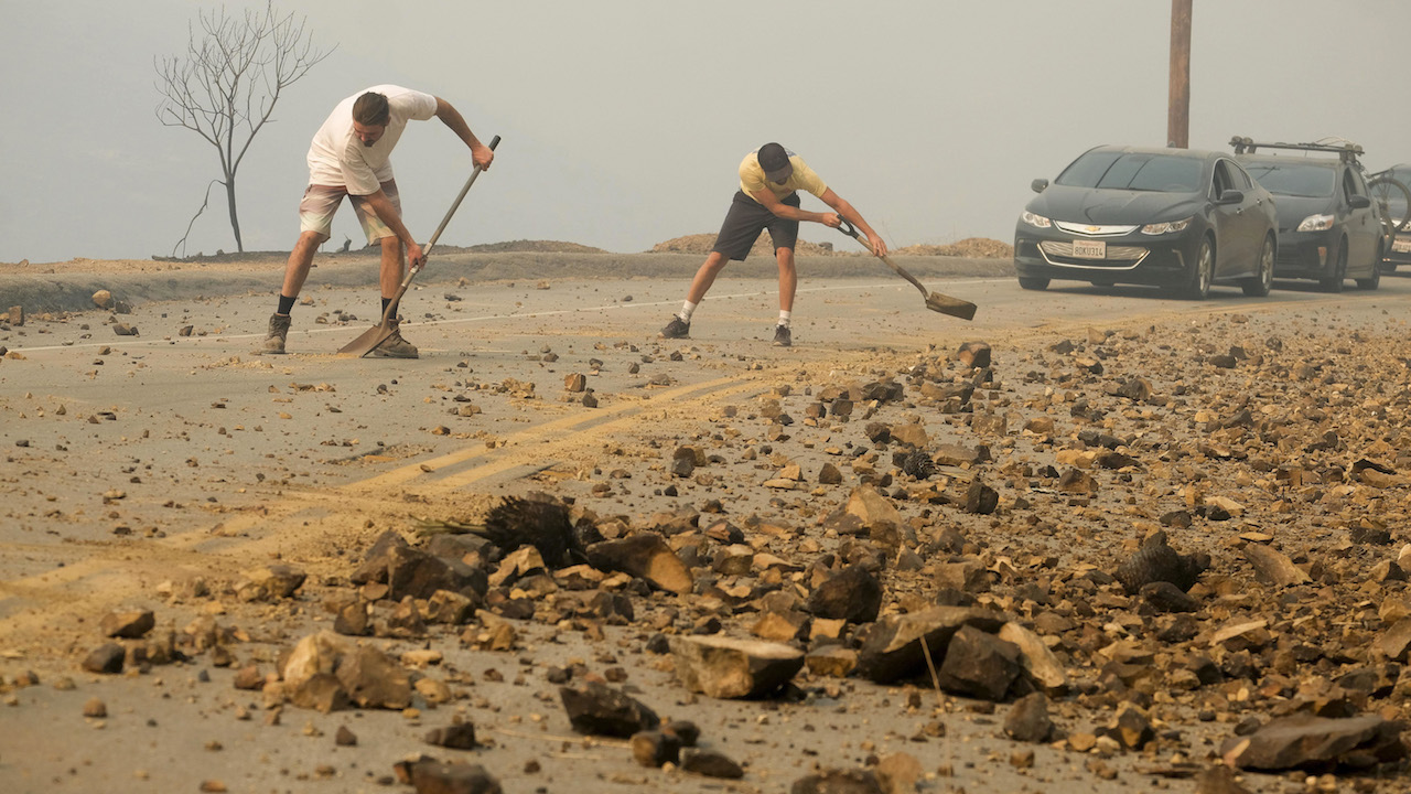 <div class='meta'><div class='origin-logo' data-origin='AP'></div><span class='caption-text' data-credit='AP Photo/Ringo H.W. Chiu'>Residents Damon Webb, left, and Brendon O'Neal clean up the road after the Woolsey fire burned in Malibu, Calif., Saturday, Nov. 10, 2018.</span></div>