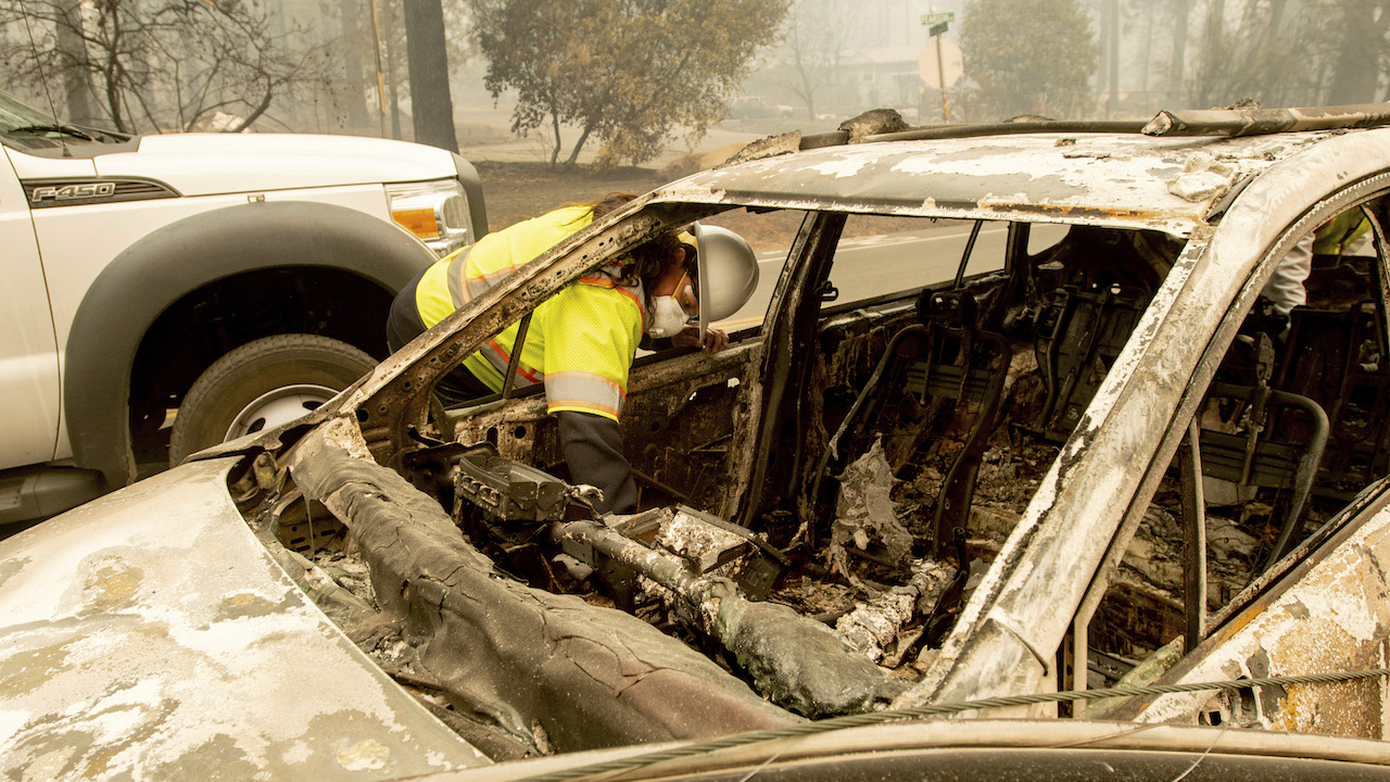 <div class='meta'><div class='origin-logo' data-origin='AP'></div><span class='caption-text' data-credit='AP Photo/Noah Berger'>Arbana Low Dog searches through a vehicle on Pearson Rd. after the wildfire burned through Paradise, Calif., on Saturday, Nov. 10, 2018.</span></div>