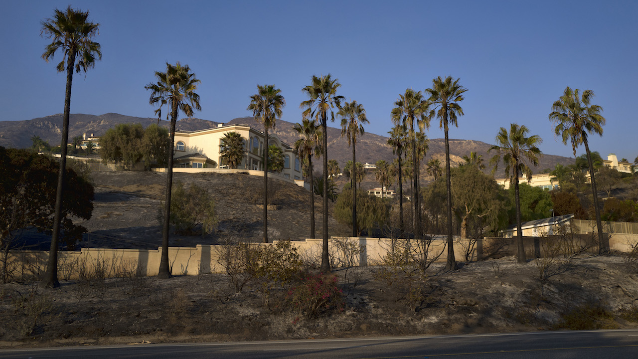 <div class='meta'><div class='origin-logo' data-origin='AP'></div><span class='caption-text' data-credit='(AP Photo/Richard Vogel)'>A house which was untouched sits on a hill behind burned palm trees lining the Pacific Coast Highway.</span></div>