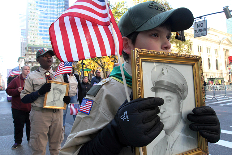 <div class='meta'><div class='origin-logo' data-origin='AP'></div><span class='caption-text' data-credit='(AP Photo/Tina Fineberg)'>Boy scout Mateo de La Roche, 11, of Carteret, New Jersey, foreground, holds an image of World War II veteran Michael Wozny, as he takes part in the NYC Veterans Day Parade.</span></div>
