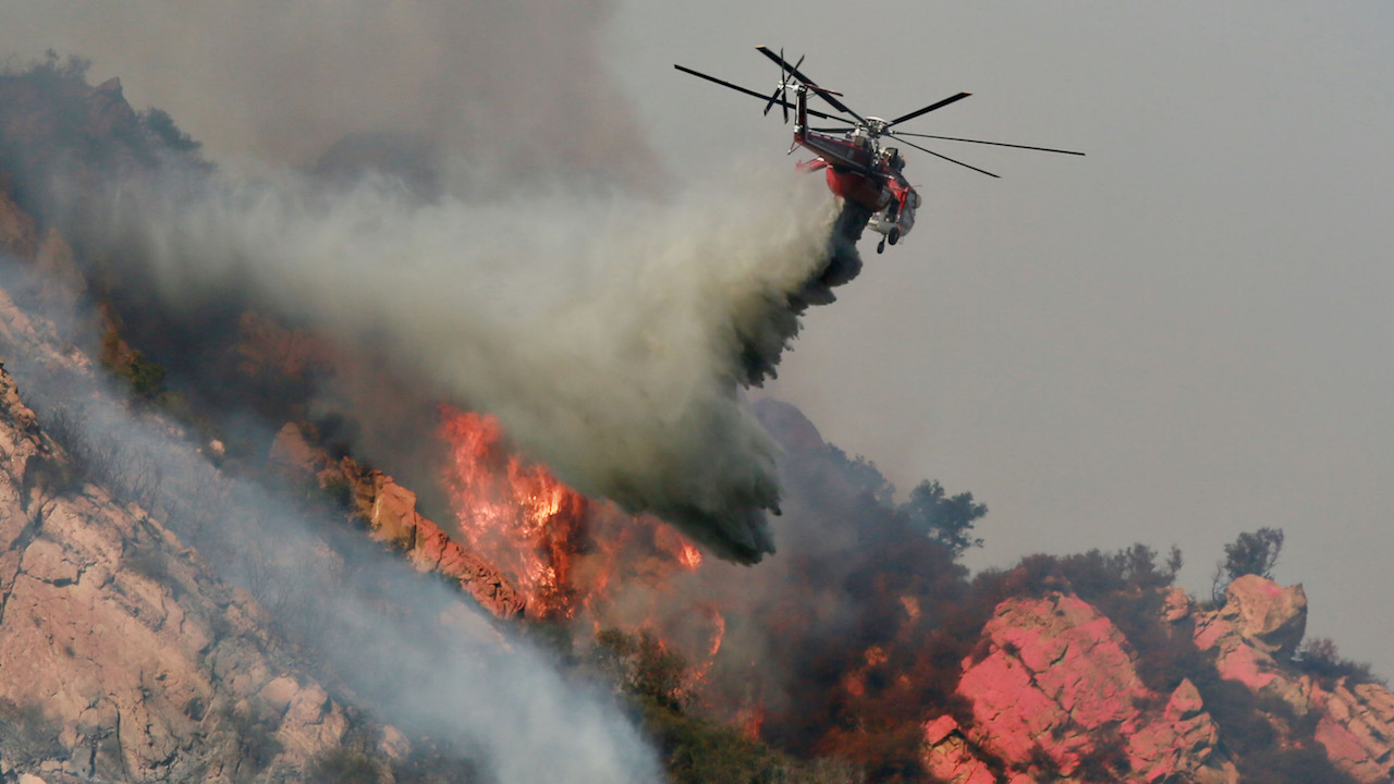 <div class='meta'><div class='origin-logo' data-origin='Creative Content'></div><span class='caption-text' data-credit='Sandy Huffaker/Getty Images'>A helicopter drops flame retardant on a wildfire on November 10, 2018, in Malibu, California.</span></div>