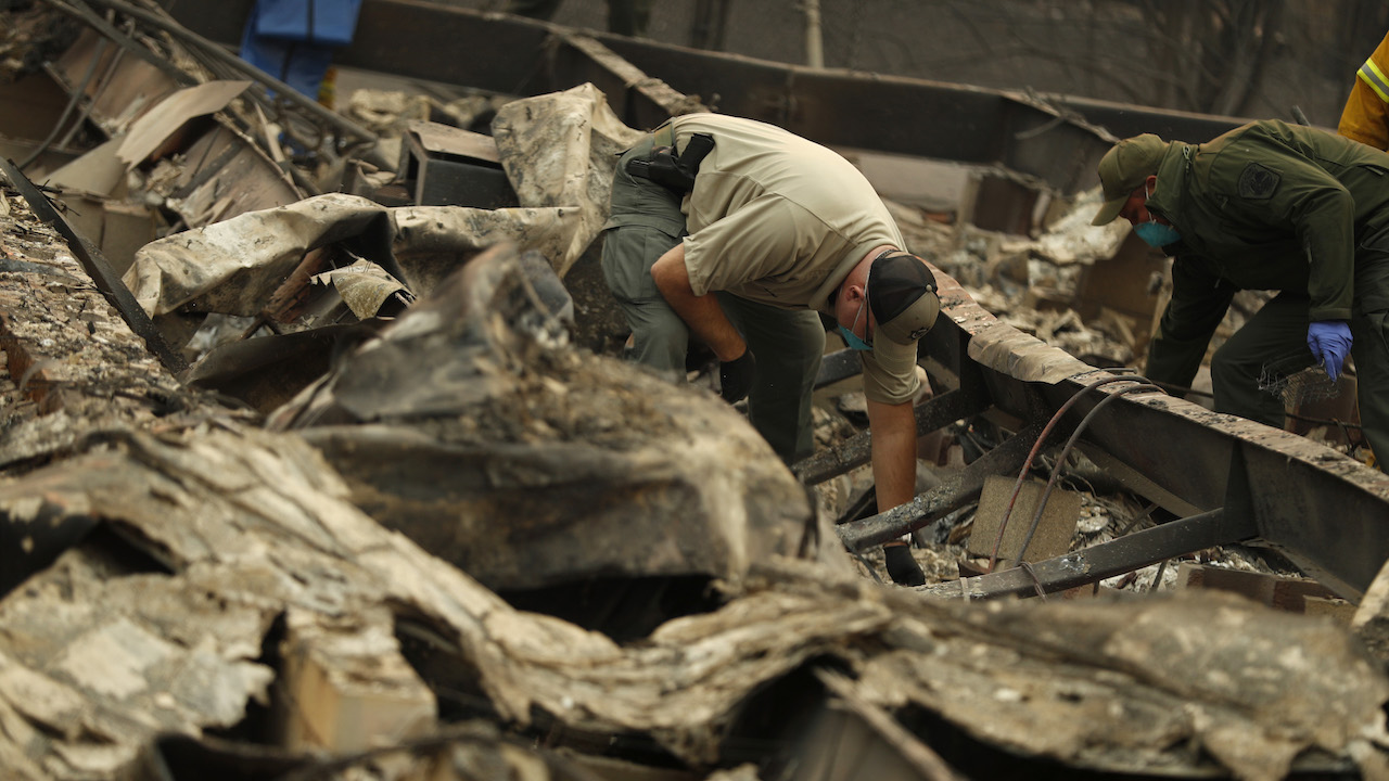 <div class='meta'><div class='origin-logo' data-origin='AP'></div><span class='caption-text' data-credit='AP Photo/John Locher'>Deputy Coroner Justin Sponhaltz, of the Mariposa County Sheriff's Office, recovers human remains found at a home destroyed by the Camp Fire, Sunday, Nov. 11, 2018.</span></div>