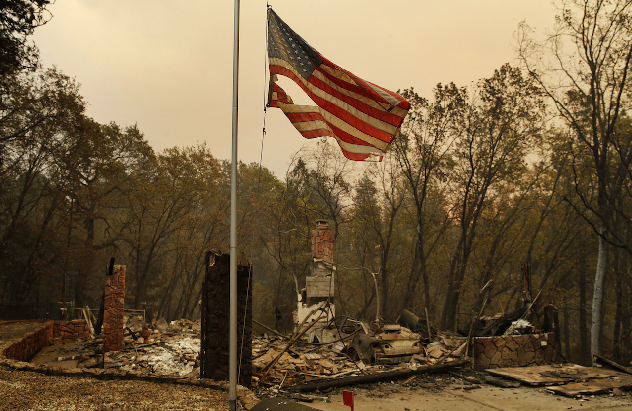 <div class='meta'><div class='origin-logo' data-origin='AP'></div><span class='caption-text' data-credit='AP Photo/John Locher'>A tattered flag flies over a burned-out home at the Camp Fire, Sunday, Nov. 11, 2018, in Paradise, Calif.</span></div>