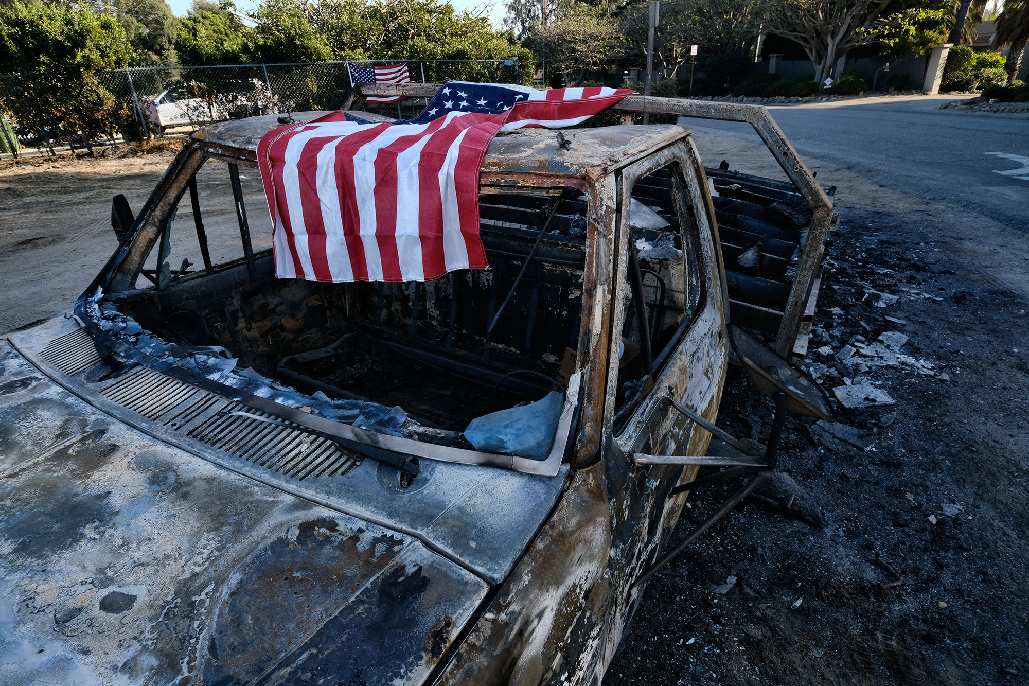 <div class='meta'><div class='origin-logo' data-origin='none'></div><span class='caption-text' data-credit='Richard Vogel/AP Photo'>An American flag is draped over the charred remains of an old pickup truck entering Point Dume along the pacific coast highway in Malibu, Calif., on Sunday Nov. 11, 2018.</span></div>