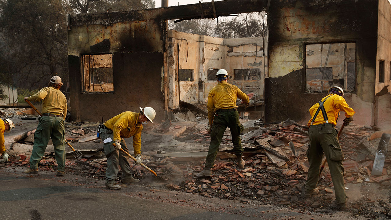 <div class='meta'><div class='origin-logo' data-origin='none'></div><span class='caption-text' data-credit='John Locher/AP Photo'>Fire crews clear rubble from the road near a building burned in the Camp Fire, Monday, Nov. 12, 2018, in Paradise, Calif.</span></div>
