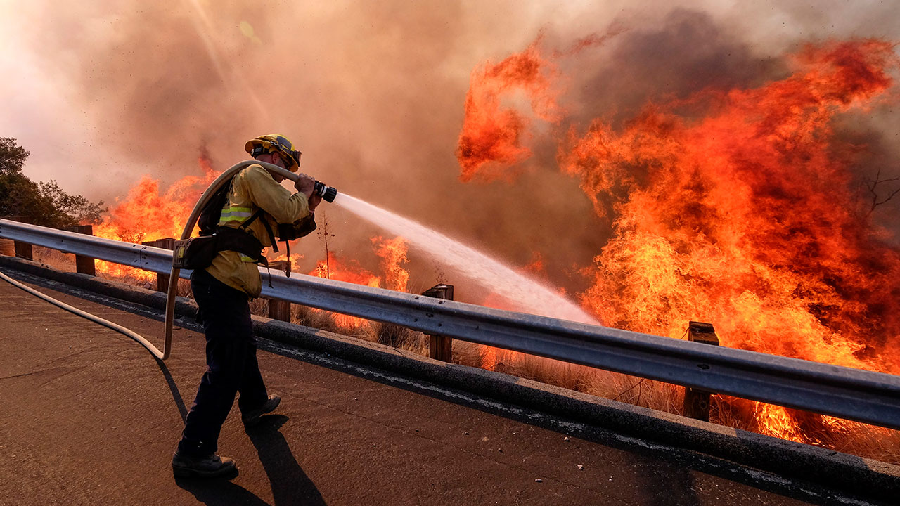 <div class='meta'><div class='origin-logo' data-origin='none'></div><span class='caption-text' data-credit='Ringo H.W. Chiu/AP Photo'>A firefighter battles a fire along the Ronald Reagan (118) Freeway in Simi Valley, Calif., Monday, Nov. 12, 2018.</span></div>