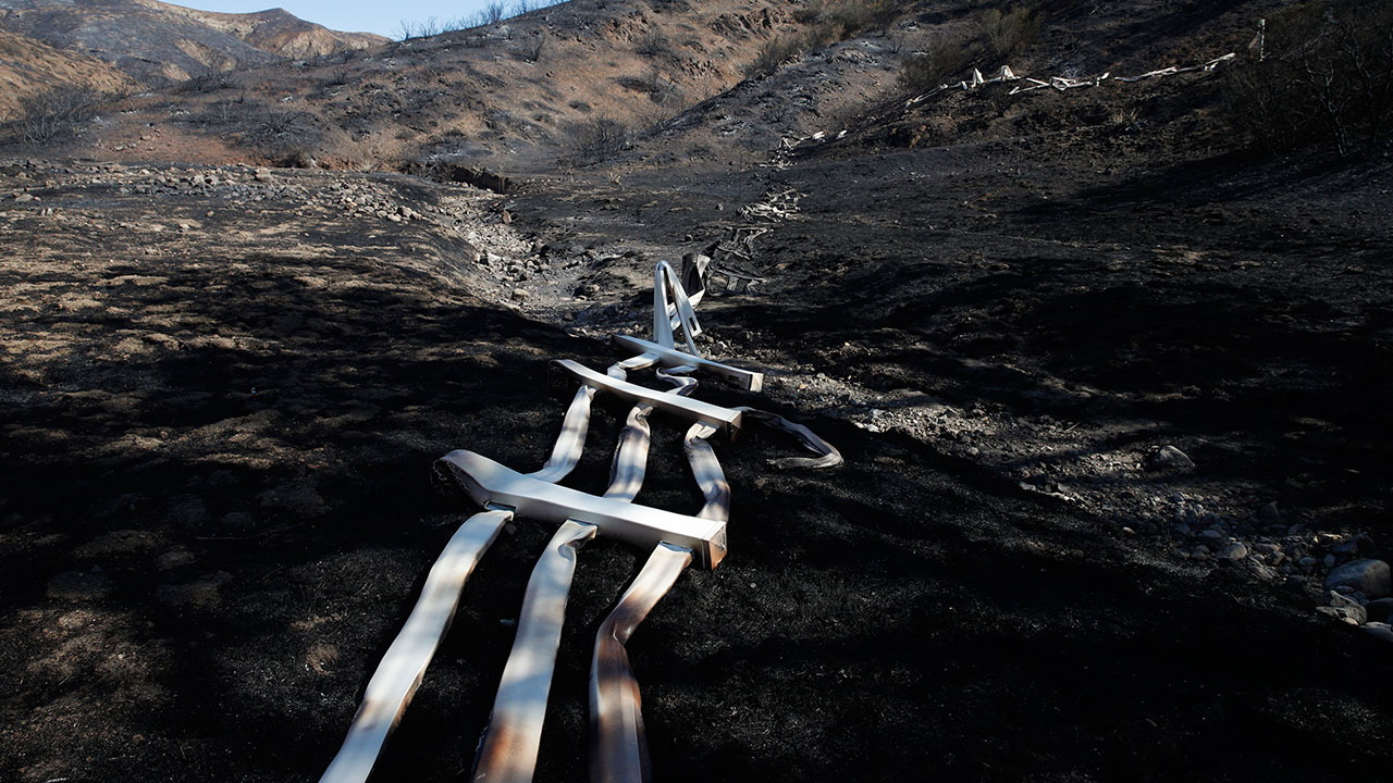 <div class='meta'><div class='origin-logo' data-origin='none'></div><span class='caption-text' data-credit='Jae C. Hong/AP Photo'>A melted fence runs along a hillside as firefighters continue to battle the Woolsey Fire burning in Southern California, Tuesday, Nov. 13, 2018, in Agoura Hills, Calif.</span></div>