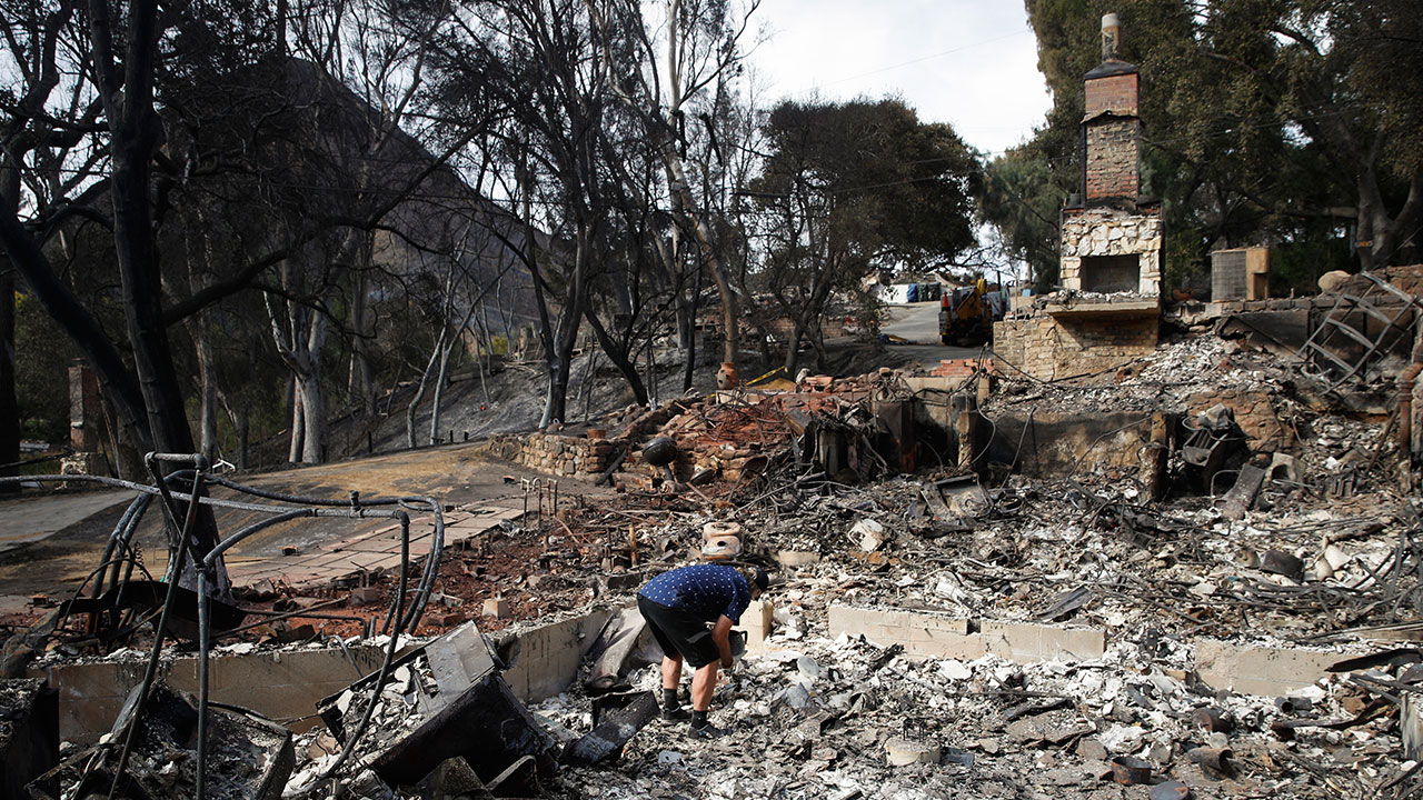 <div class='meta'><div class='origin-logo' data-origin='none'></div><span class='caption-text' data-credit='Jae C. Hong/AP Photo'>Roger Kelton searches through the remains of his mother-in-law's home leveled by the Woolsey Fire, Tuesday, Nov. 13, 2018, in the southern California city of Agoura Hills.</span></div>