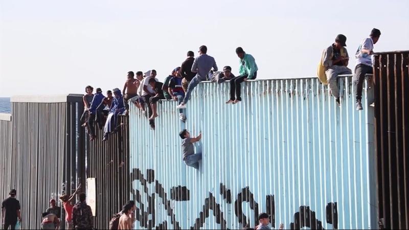 Migrants climb wall as caravan arrives at US border in Tijuana, Mexico - ABC13 Houston