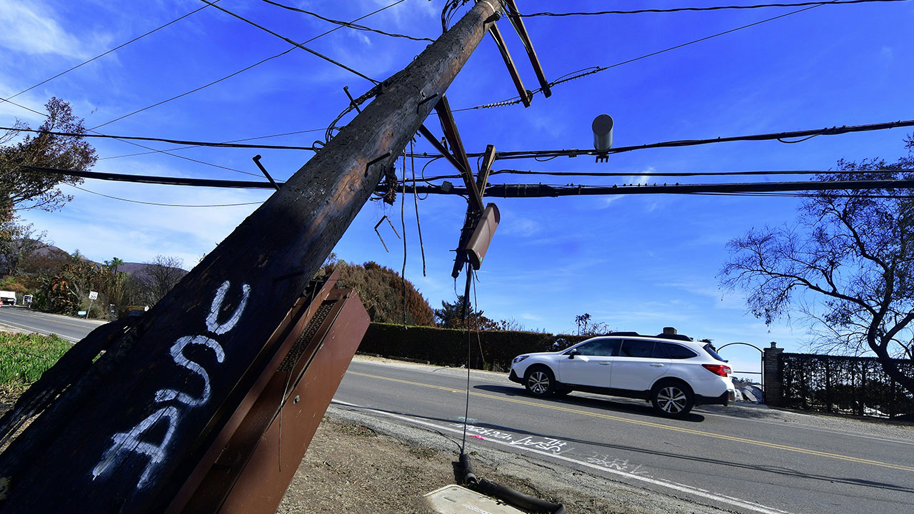 <div class='meta'><div class='origin-logo' data-origin='none'></div><span class='caption-text' data-credit='FREDERIC J. BROWN/AFP/Getty Images'>Downed power lines and poles, casualties of the Woolsey Fire, on Busch Drive in Malibu, California on November 13, 2018.</span></div>