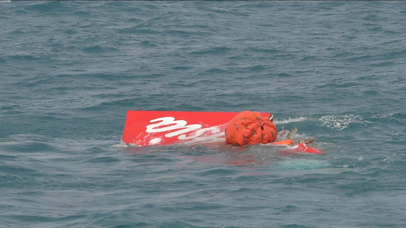 Portion of the tail of AirAsia Flight 8501 floats on the water as Indonesian navy divers conduct search operations for the black boxes of the crashed plane in the Java Sea, Indonesia, Saturday, Jan. 10, 2015.