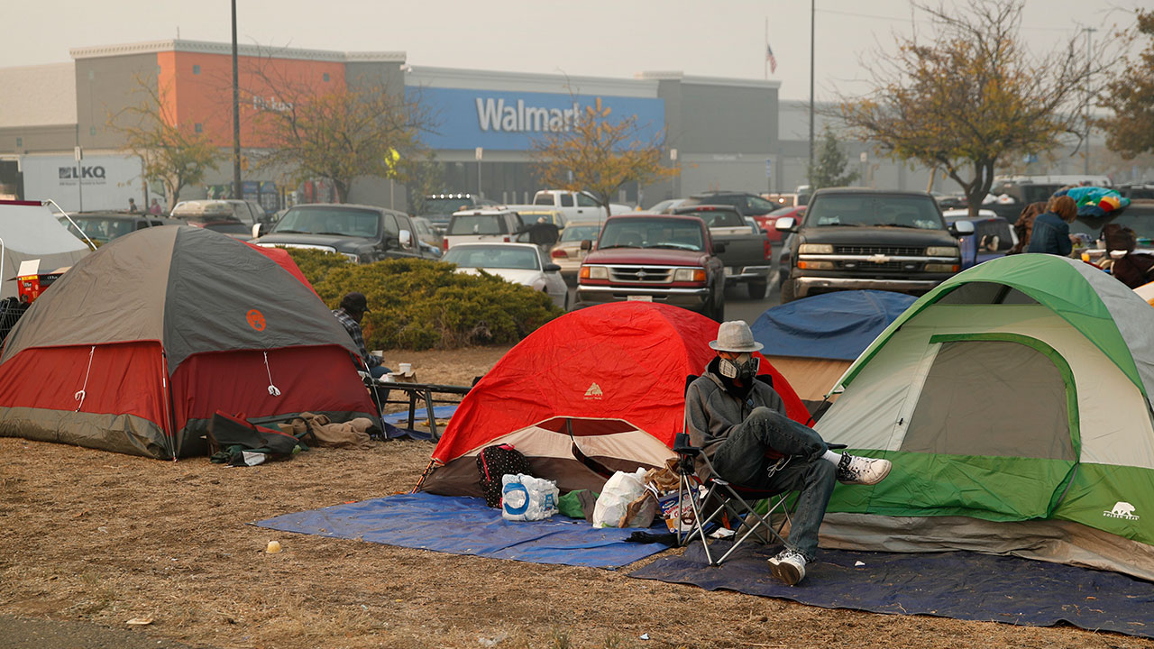 <div class='meta'><div class='origin-logo' data-origin='none'></div><span class='caption-text' data-credit='John Locher/AP Photo'>People sit by their tents at a makeshift encampment outside a Walmart store for people displaced by the Camp Fire, Friday, Nov. 16, 2018, in Chico, Calif.</span></div>