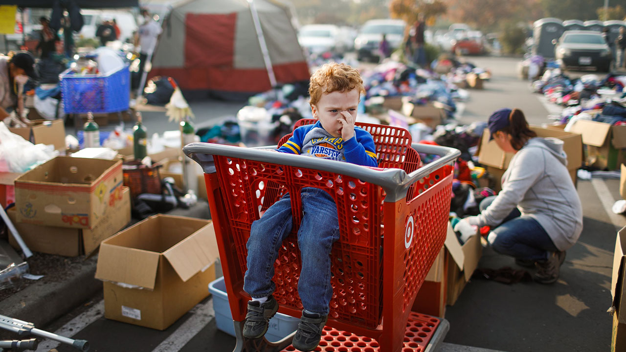 <div class='meta'><div class='origin-logo' data-origin='none'></div><span class='caption-text' data-credit='Gabrielle Lurie / San Francisco Chronicle / Polaris via Getty'>Evacuee Josaiah Darby, 3, waits in a shopping cart as his mother Autumn Darby (right) looks through items at the Target parking lot.</span></div>