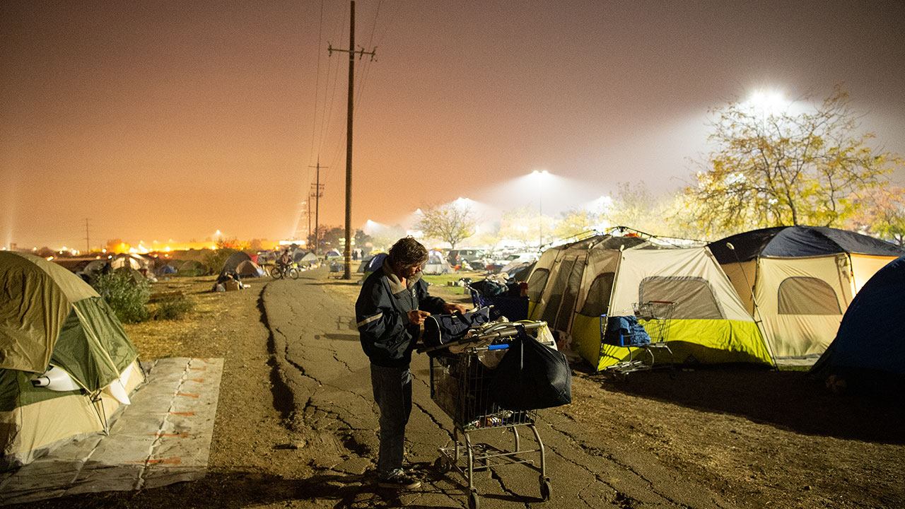 <div class='meta'><div class='origin-logo' data-origin='none'></div><span class='caption-text' data-credit='Josh Edelson for the Washington Post'>A man tends to his belongings at an evacuee encampment at a Walmart parking lot in Chico, California on November 19, 2018.</span></div>