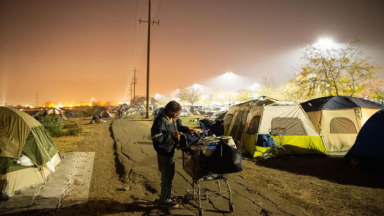 <div class='meta'><div class='origin-logo' data-origin='none'></div><span class='caption-text' data-credit='Josh Edelson for the Washington Post'>A man tends to his belongings at an evacuee encampment at a Walmart parking lot in Chico, California on November 19, 2018.</span></div>