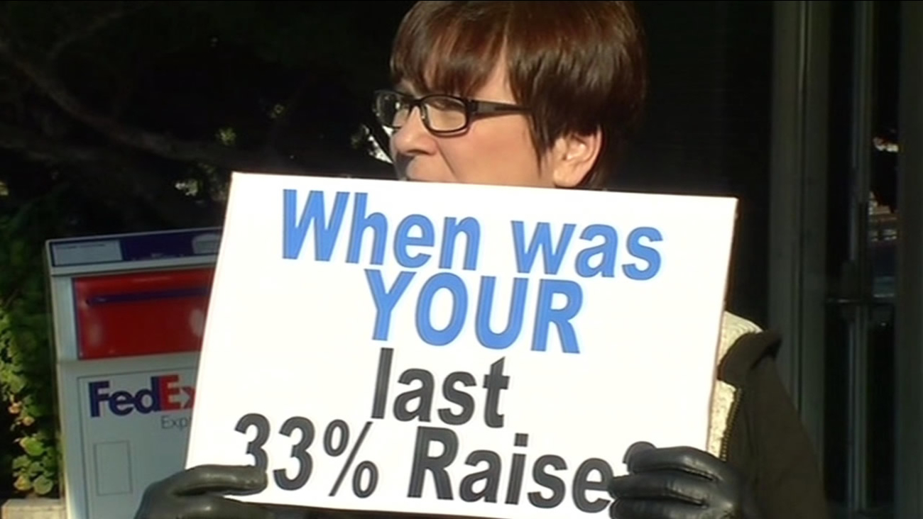 A woman holds a sign protesting a pay hike that Contra Costa County supervisors voted to give themselves.